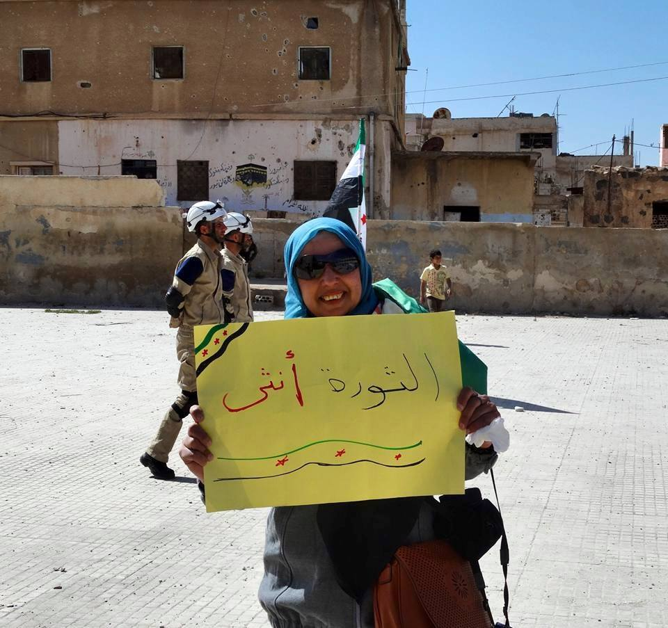 """Woman in Daraa holds sign saying """"The Revolution is Female"""""""