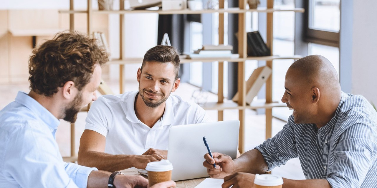 Causal businessmen work together around a table with paper and coffe cups