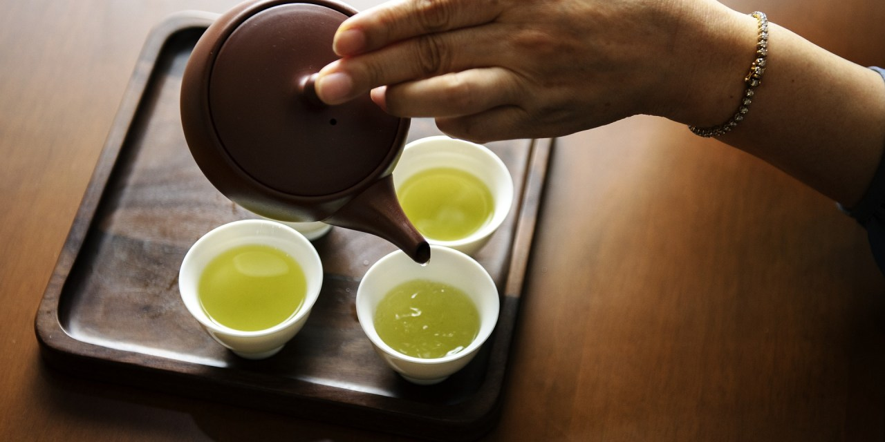 shots of green tea are poured into delicate, white teacups from a small, brown teapot