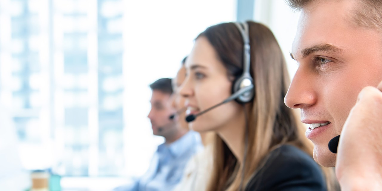 Call center representatives chat on headsets