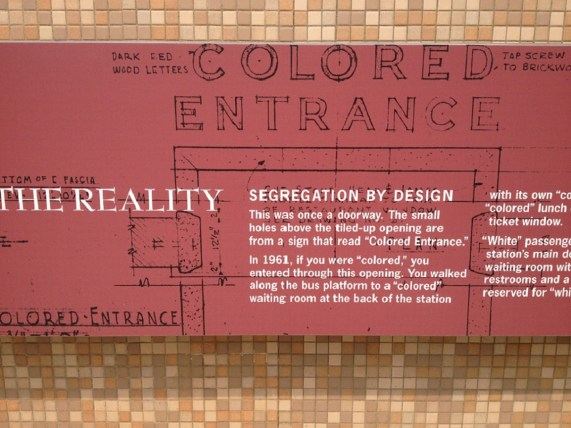 """A sign across the panel now covering the old """"Colored Entrance"""" to the former Greyhound bus station in Montgomery explains its significance. (contributed)"""