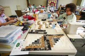 With strips of coordinated fabrics laid out in order of sewing, a traditional pieced quilt design, like these two log cabin blocks, were sewn by Ella Thomas, right, at the retreat. Susan Wagner, left, begins piecing of a contemporary-style quilt. (Meg McKinney / Alabama NewsCenter)
