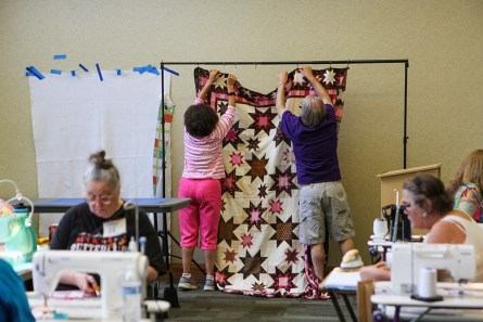 Ella Thomas, left, and Larry Cartwright hang one of Thomas' quilt tops for display, as quilters work at their machines. Quilts and tops were displayed for inspiration. (Meg McKinney / Alabama NewsCenter)
