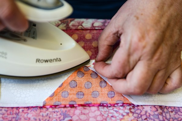Pressing seam edges so they lay flat, no matter how small, is part of quilt making. (Meg McKinney / Alabama NewsCenter)