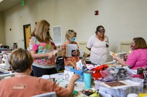 Susan Hill Lee, right, presents paper piecing techniques for, standing left to right, Vicki Moore, Peggy Plyler and Kimmie Monteabaro. The retreat included educational demonstrations. (Meg McKinney / Alabama NewsCenter)