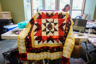 A completed top by Hilda Childress, draped over a sewing machine, is one of many quilts and projects worked on at the retreat. (Meg McKinney / Alabama NewsCenter)