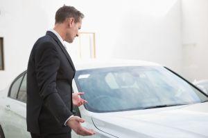 businessman looking at broken down car