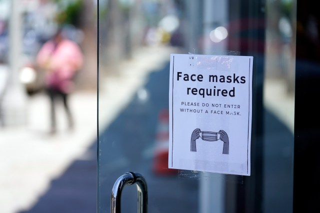 A sign advises shoppers to wear masks outside of a store on July 19 in the Fairfax district of Los Angeles.