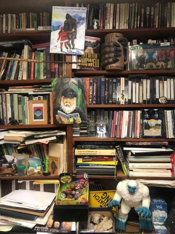 Shelves lined with bigfoot books, VHS tapes, and artifacts