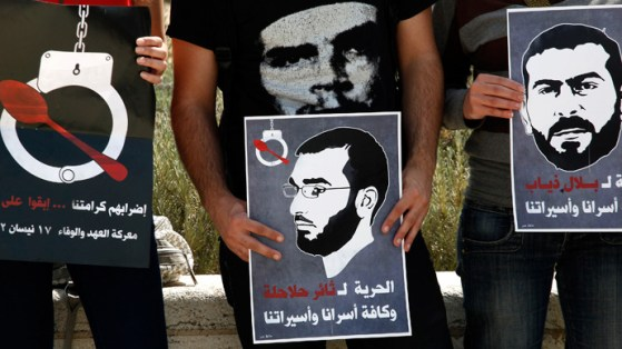 Israeli Arab protesters hold posters depicting Palestinian hunger strikers Thaer Halahla and Bilal Thiab (R) who are in administrative detention during a protest outside Israel's Supreme Court in Jerusalem on May 3, 2012 (AFP Photo / Gali Tibbon)