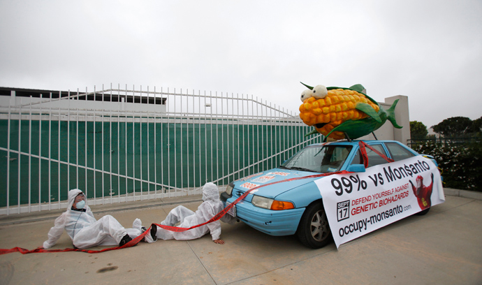 Protesters against Genetically Modified Organisms (GMO) are chained to a vehicle as they block a delivery entrance to a Monsanto seed distribution facility in Oxnard, California (Reuters / Mario Anzuoni)