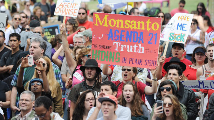 People carry signs during a protest against agribusiness giant Monsanto in Los Angeles on May 25, 2013. (AFP Photo / Robin Beck)