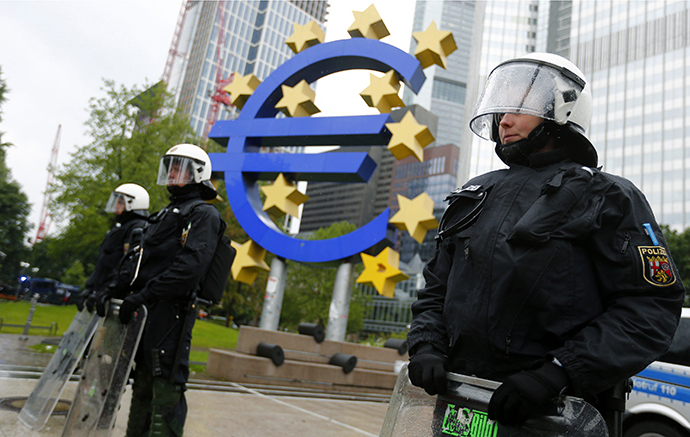 """Riot police stand near the euro sign in front of the European Central Bank (ECB) headquarters during an anti-capitalist """"Blockupy"""" demonstration in Frankfurt May 31, 2013. (Reuters / Kai Pfaffenbach)"""
