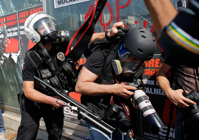 A Turkish riot policeman pushes a photographer during a protest at Taksim Square in Istanbul June 11, 2013 (Reuters / Murad Sezer)