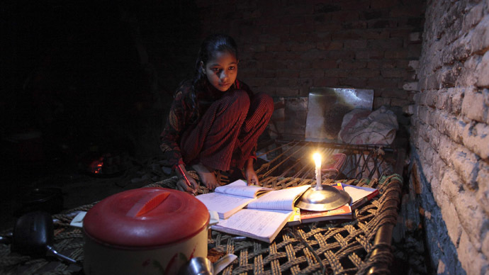 Noreen, 13, uses candlelight as she studies during a power outage in a slum in Islamabad April 29, 2013. (Reuters)