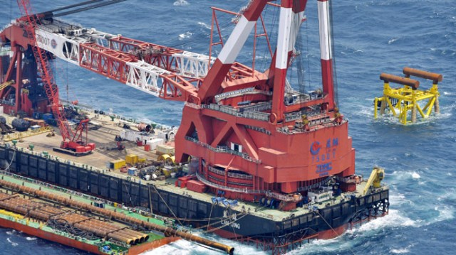 An aerial view shows a Chinese facility under construction (top R) for natural gas exploration and a large crane ship are seen near what Tokyo claims to be the median line between the overlapping exclusive economic zones of Japan and China, in the East China Sea, in this photo taken by Kyodo July 5, 2013. (Reuters/Kyodo)