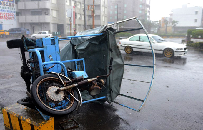 A three-wheeled vehicle lies on its side after being blown over by winds from Typhoon Usagi in the town of Hengtsun in southeast Pingtung county on September 21, 2013 as the storm sweeps past the southern parts of the island. (AFP Photo / Sam Yeh)