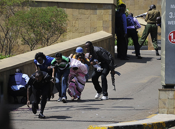 A policeman carry's a baby to safety after masked gunmen stormed an upmarket mall and sprayed gunfire on shoppers and staff, killing at least six on September 21, 2013 in Nairobi. (AFP Photo / Simon Maina)