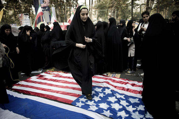 An Iranian woman steps on a US flag outside the former US embassy in Tehran on November 4, 2013, during a demonstration to mark the 34th anniversary of the 1979 US embassy takeover. (AFP Photo / Behrouz Mehri)