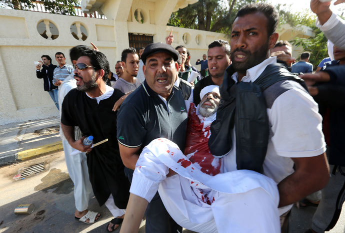 People assist a man who was injured after Libyan militiamen opened fire on a crowd wanting them to move out of their headquarters on November 15, 2013 in southern Tripoli. (AFP Photo / Mahmud Turkia)