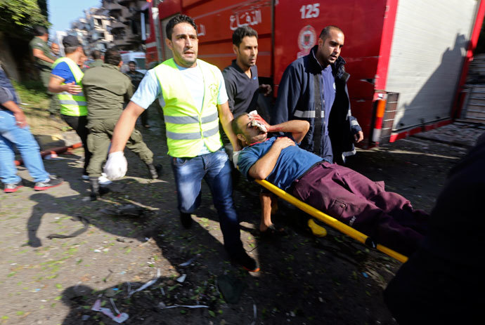 Civil defence personnel carry a wounded man at the site of explosions near the Iranian embassy in Beirut November 19, 2013.(Reuters / Hasan Shaaban)