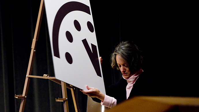 A depiction of the Doomsday Clock is removed following an announcement by the Bulletin of Atomic Scientists (BAS) announcing that it has moved the hands to five minutes to midnight, up one minute from two years ago, at the American Association for the Advancement in Washington, DC (AFP Photo / Saul Loeb)