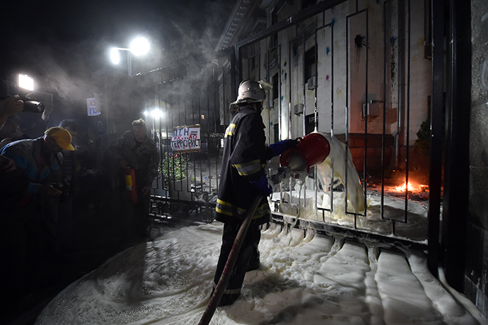 A fireman extinguishes the flames from a Molotov coctail thrown by a protester during rally against the Russian President Vladimir Putin in front of the Russian Embassy in Kiev on June 14, 2014 (AFP Photo / Sergey Supinsky)