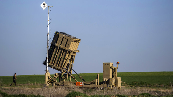 An Israeli soldier walks near the launcher of an Iron Dome missile interceptor battery deployed in the southern Israeli coastal city of Ashkelon (Reuters/Amir Cohen)