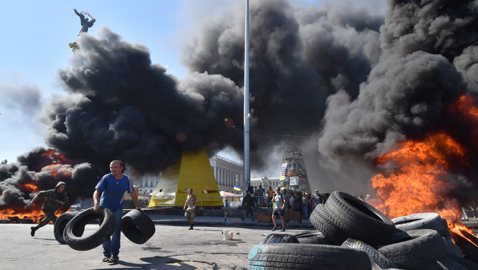 A man holds tires as Maidan self-defence activists clash with fighters of Kiev-1 volunteer battalion on Independence Square in Kiev on August 7, 2014.(AFP Photo / Sergei Supinsky )