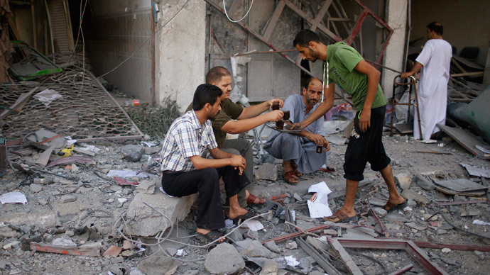 Palestinians drink coffee outside a damaged house as they look at the remains of a tower building housing offices, which witnesses said was destroyed by an Israeli air strike, in Gaza City August 26, 2014.(Reuters / Mohammed Salem)