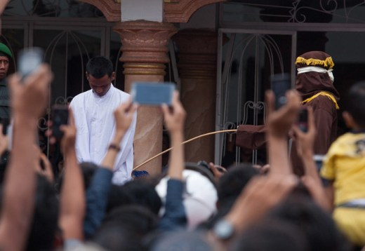 This picture taken in Banda Aceh on September 19, 2014 shows a hooded official (R, brown) caning an Aceh man for gambling in Aceh. Lawmakers in Indonesia's Aceh will vote on September 26 on whether to make gay sex punishable by 100 lashes of the cane, the latest proposed Islamic regulation in the conservative province that has outraged rights activists. (AFP Photo/Chaideer Mahyuddin)