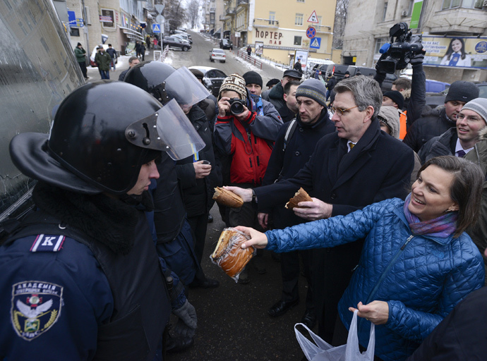 U.S. Assistant Secretary of State for European and Eurasian Affairs Victoria Nuland (R) and U.S. Ambassador Geoffrey Pyatt (2nd R) distribute bread to riot police near Independence square in Kiev December 11, 2013. (Reuters / Andrew Kravchenko)