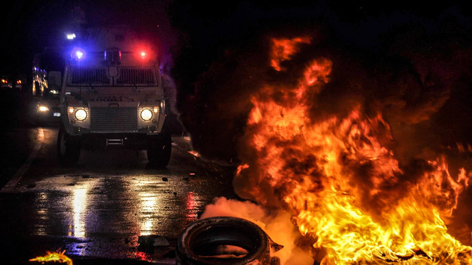 Flames are seen near a Turkish police vehicle on October 7, 2014 in the southeastern city of Diyarbakir during a demonstration of Kurdish to demand more western intervention against Islamic State militants (IS) in Syria and Iraq.(AFP Photo / Ilyas Akengin)
