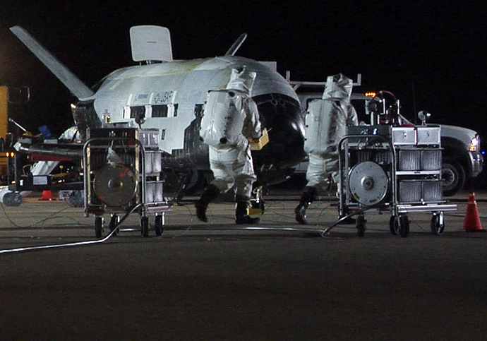Personnel in self-contained atmospheric protective ensemble suits conduct initial checks on the X-37B Orbital Vehicle (Reuters / HO)
