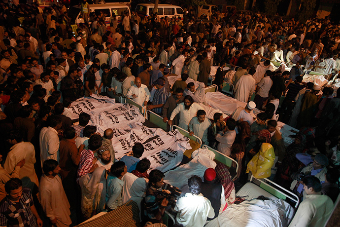 Pakistani relatives gather beside the covered bodies of victims who were killed in suicide bomb attack in Wagha border near Lahore November 2, 2014 (Reuters / Mohsin Raza)