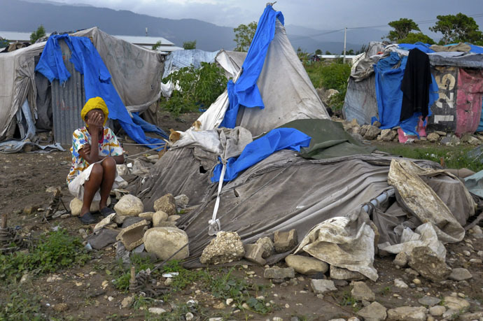 A Haitian woman living in a tent camp for people affected by the January 2010 earthquake covers her face as she reacts after her tent home was destroyed by Tropical Storm Isaac outside of Port-au-Prince August 26, 2012. (Reuters/Swoan Parker)