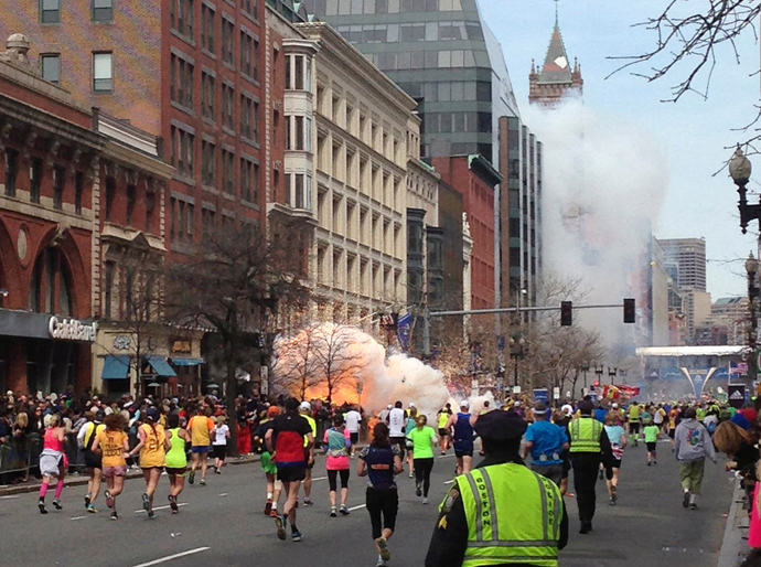 Runners continue to run towards the finish line of the Boston Marathon as an explosion erupts near the finish line of the race in this photo exclusively licensed to Reuters by photographer Dan Lampariello after he took the photo in Boston, Massachusetts, April 15, 2013 (Reuters / Dan Lampariello)