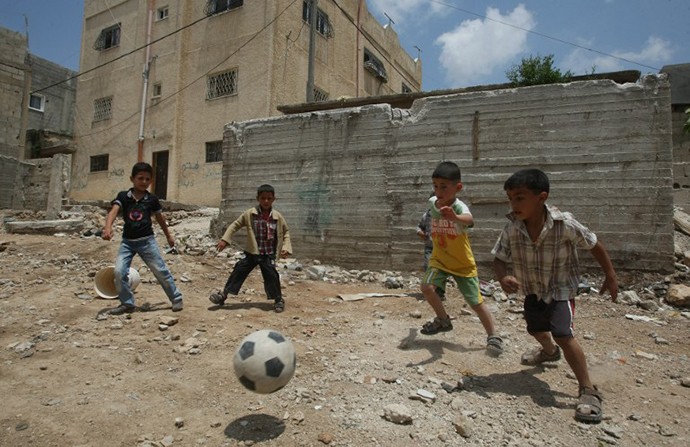 Palestinian boys play football outside their homes at the refugee camp of al-Fawar in the West Bank town of Hebron on May 14, 2012. (AFP Photo / Hazem Bader)