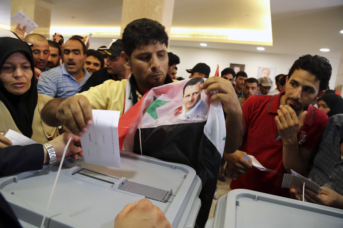 A Syrian national living in Beirut casts his vote ahead of the June 3 presidential election as he holds a Syrian national flag with Syria's President Bashar al-Assad's picture on it at the Syrian Embassy in Yarze, east of Beirut May 28, 2014. (Reuters)