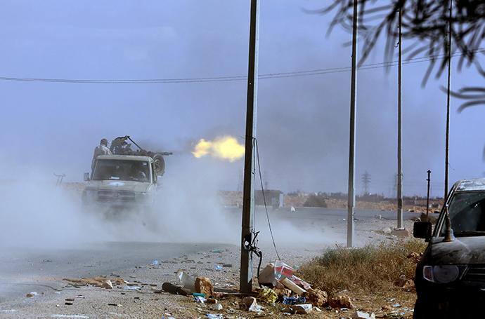 Pro-government forces fire their gun off the back of a truck on October 23, 2012, one kilometer from the northern entrance to the town of Bani Walid, one of the final bastions of Moamer Kadhafi's ousted regime (AFP Photo)
