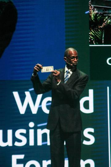 Ian Williamson, experto en liderazgo, muestra a la audiencia un billete de un dólar.