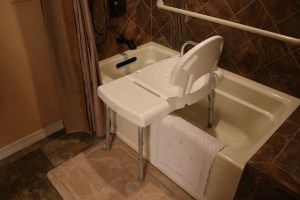 A bathroom with a shower chair and a grab bar in the shower.