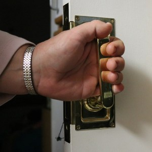 Closeup of a person's hand on a lever-style door handle