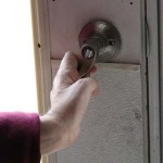 Closeup of a hand grasping a lever doorhandle.