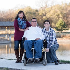 A family of a man using a wheelchair, a woman, and a young man pose together outside.