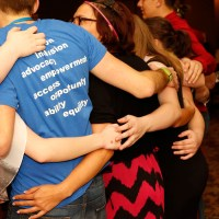 Youth put their arms around each other as part of a group activity