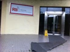 """Die Holzverbarrikadierung vor der Eingangstür ist bereits entfernt worden - nur noch ein Schild """"Vorsicht Rutschgefahr"""" erinnert an den abgezogenen Taifun"""