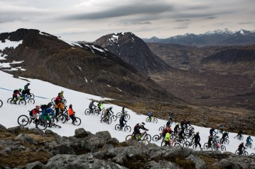 Mountain bikers race down snow slope with mountain background
