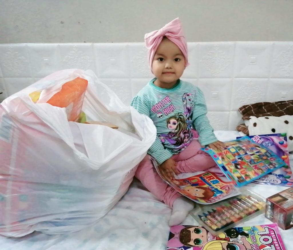Ein leukämiekrankes Mädchen im Krankenhaus in Peru spielt mit Zeitschriften.