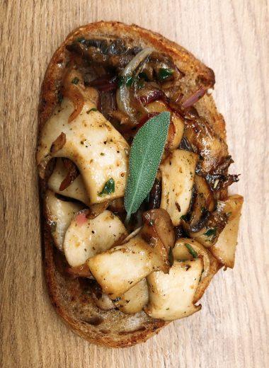 Eine Scheibe Brot mit gebratenen Pilzen und einem Salbeiblatt